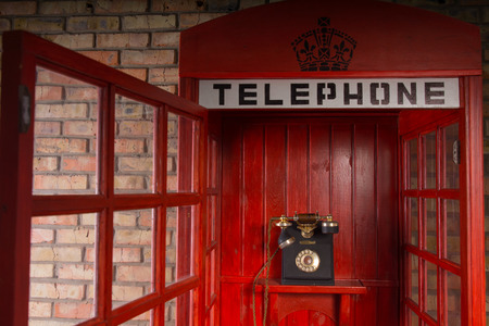 pay wall: Close Up Detail of Red Public Telephone Booth with Old Fashioned Telephone Inside and Open Door Stock Photo