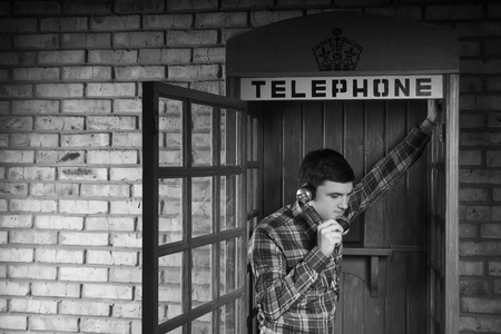 pay wall: Young Man Calling Someone at the Telephone Booth with Brick Wall Background. Captured in Monochrome.