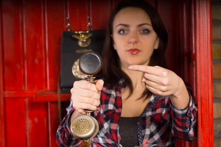 viewer: Young woman indicating an incoming phone call as she holds a vintage handset towards the viewer and points at it with her finger