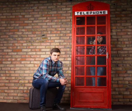 frantic: Bored young man waiting for his wife or girlfriend to finish chatting on the phone in a red British phone booth sitting patiently outside on his suitcase Stock Photo