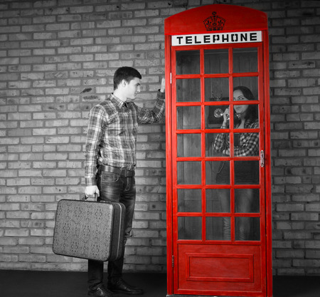 frantic: Young Handsome Man Holding Suitcase Knocking at the Telephone Booth with Woman Talking Inside. Captured with Gray Scale Effect.