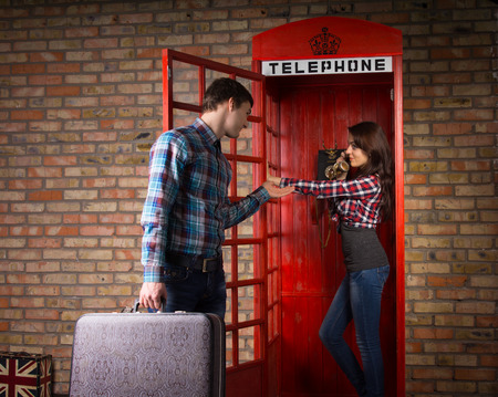 imploring: Young man imploring his wife to get off the phone as he stands outside the telephone booth with his suitcase in his hand