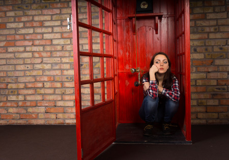 Bored young woman waiting for a call in a public telephone booth sitting on the floor with a grumpy expression