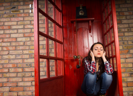unemotional: Upset woman sitting blocking her ears in a telephone booth as the handset dangles alongside her ear