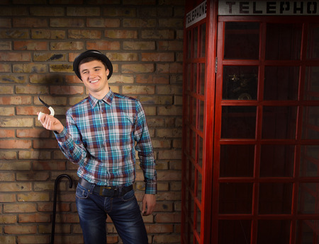 characterization: Happy Young Handsome Man in Checkered Shirt and Jeans with Trendy Hat Holding Smoking Pipe Near Telephone Booth on a Brick Wall Background.