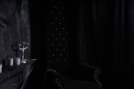 eerie: Plush Black High Back Chair and Candelabras with Cobwebs in Eerie Halloween Haunted House Setting Stock Photo