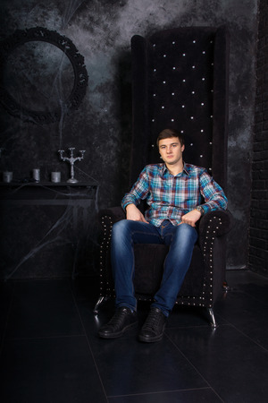eerie: Man Wearing Casual Clothing Sitting in High Back Chair in Eerie Halloween Haunted House Setting with Candelabras and Cobwebs