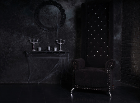 Black High Back Chair and Cobweb Covered Candelabras in Eerie Halloween Haunted House Setting Imagens - 35090997