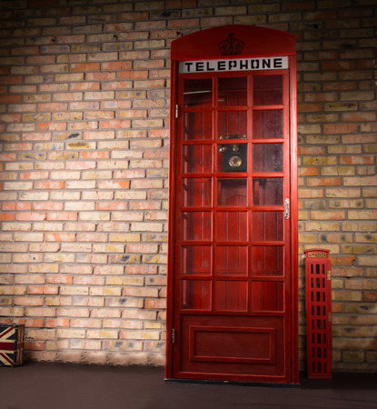 pay wall: Replica iconic British telephone booth standing against a brick wall with a telephone sign and crown on the front Stock Photo