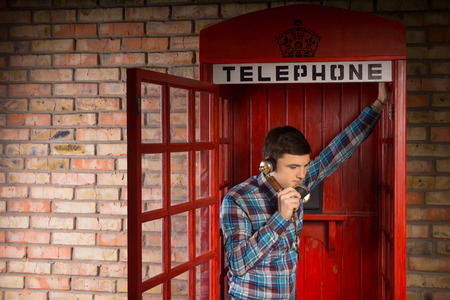 pay wall: Man chatting inside a red British telephone booth leaning in the open doorway listening to the conversation