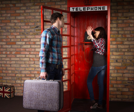 make public: Woman refusing to listen to her husband as he implores her to get off the phone in a public telephone booth as he has a trip to make with his suitcase Stock Photo