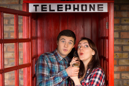 gleeful: Young couple enjoying a gossip as they stand close together in a phone booth sharing the handset and gasping in gleeful anticipation at a juicy tit bit of news