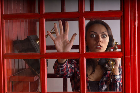 wide eyed: Terrified woman trapped in a telephone booth staring out with a wild wide eyed expression of panic as she holds the vintage handset in her hand Stock Photo