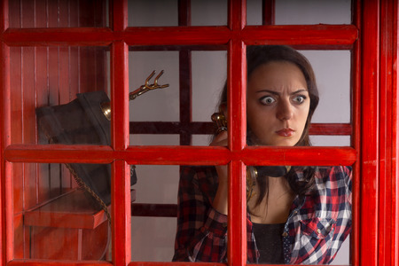 chats: Young woman with a horrified expression peering out of the glass window pane on a public telephone booth as she chats on a vintage phone