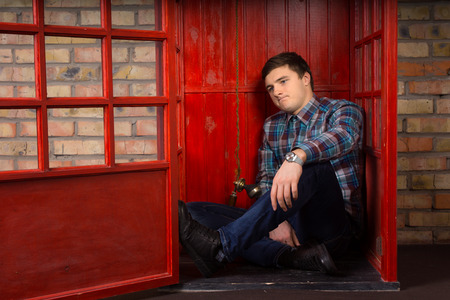 he is public: Frustrated young man waiting for a telephone call as he sits on the floor of a public phone booth frowning in annoyance