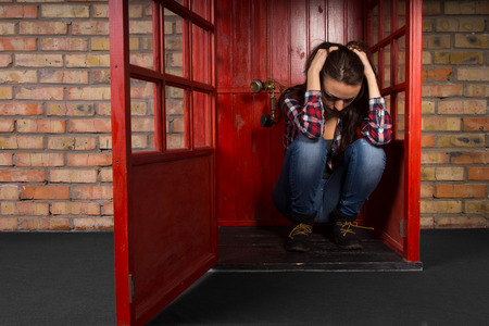 lady on phone: Depressed young woman crouched on the floor sitting in a phone booth with her head in her hands as the handset dangles alongside her ear Stock Photo