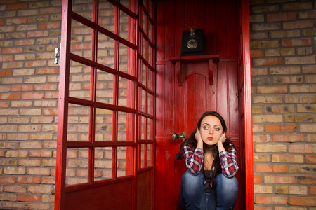 hands over ears: Troubled Young Woman with Hands Over Ears Crouching in Red Telephone Booth with Open Door