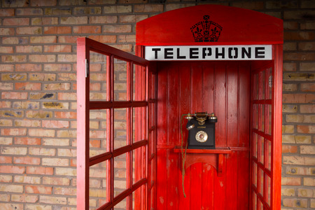verbal: Close Up of Red Telephone Booth with Old Fashioned Telephone and Open Door Stock Photo