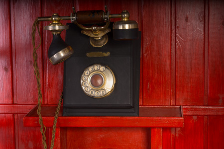 Old retro vintage rotary dial-up telephone instrument with a handset and cradle mounted on a red wooden wall Stock fotó
