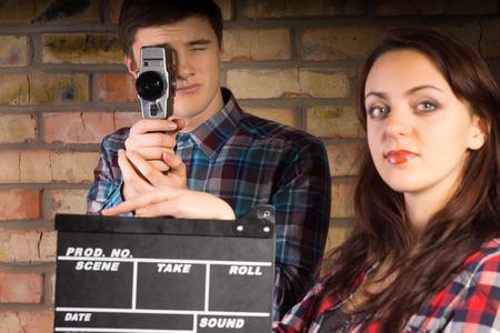 hombre disparando: Mujer sosteniendo una claqueta listo para el camarógrafo detrás de ella para iniciar la acción y comenzar la filmación o grabación, el hombre joven que sostiene la cámara retro
