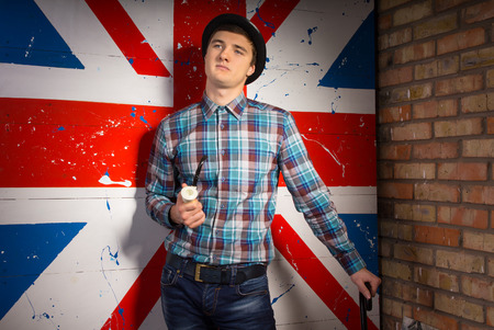 characterization: Young Handsome Man in Checkered Shirt and Jeans Outfit with Smoking Pipe and Cane Posing In Front Huge UK Flag Print