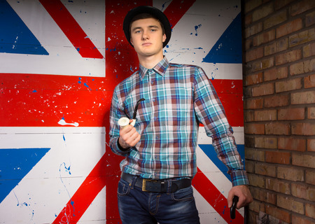 characterization: Close up Portrait of Gorgeous Young Man in Trendy Outfit with Tobacco Pipe and Cane in Front UK Flag Print While Looking at the Camera.