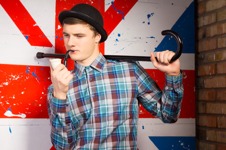 sombre: Close up Young Handsome Man in Trendy Fashion Posing with Smoking Pipe and Cane on his Shoulder in Front Britain Flag Print. Stock Photo