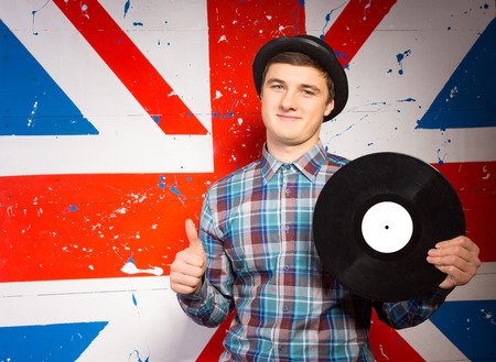 olden day: Close up Smiling Young Man in Checkered Long Sleeve Shirt and Hat Holding Vinyl Record Showing Thumbs Up While Looking at the Camera. Captured on Britain Flag Print Background.