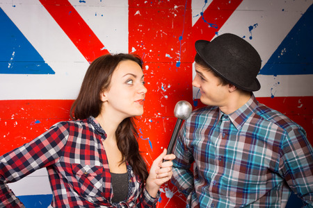 Two performers doing a British comedy show standing in front of a Union Jack painted on a wall using a microphone wearing patriotic clothing and a bowler hat 스톡 콘텐츠