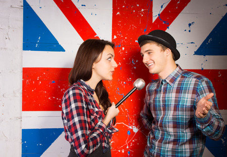 talk show: Close up Young Woman Interviewing Happy Handsome Young Man in Trendy Fashion Using Microphone, In Front British Flag Print.