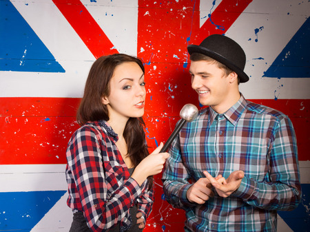 talk show: Female British chat show host interviewing a handsome young man in a bowler hat in front of a Union Jack flag painted on the wall Stock Photo