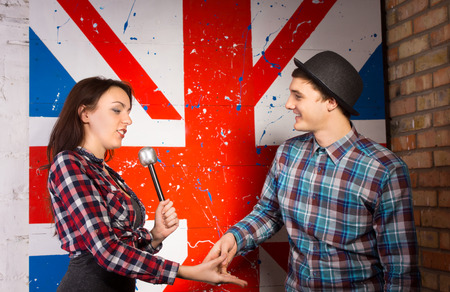 talk show: Half Body Shot of Interviewer Woman About to Shake Hands with Interviewee Man, in Both Casual Attire, on Huge British Flag Print.