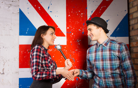 talk show: Happy Interviewer Woman with Microphone Shaking Hands with Guest in Trendy Fashion in front British Flag Print.