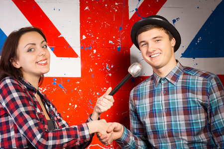 talk show: Close up Happy Young Man and Woman, with Microphone, in Checkered Shirts Shaking their Hands In Front Camera. Captured in Front Big British Flag Print Stock Photo