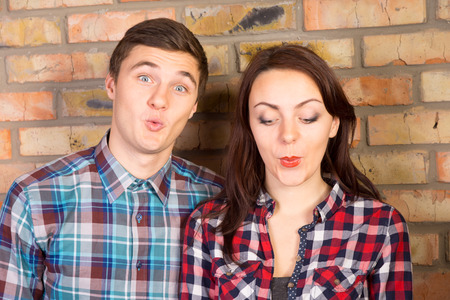 puckering lips: Close Up of Young Couple Puckering Lips and Standing in front of Brick Wall Stock Photo