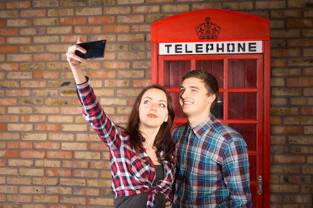 cell phone booth: Young Couple Wearing Plaid Shirts Taking Self Portrait with Cell Phone in front of Red Telephone Booth Stock Photo