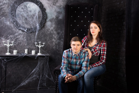 festooned: Young Couple Wearing Plaid Shirts Sitting Together in High Back Chair in Eerie Haunted House Setting