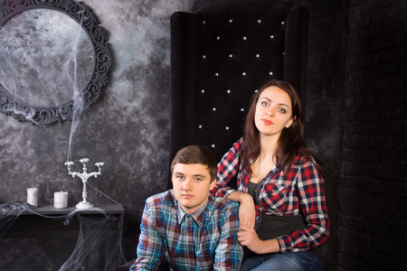 festooned: Close Up of Young Couple Wearing Plaid Shirts Sitting in Black High Back Chair in Haunted House Setting
