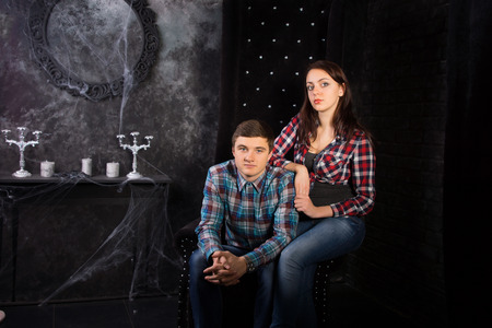 festooned: Young Couple Wearing Plaid Shirts Sitting in Black High Back Chair in Haunted House Setting