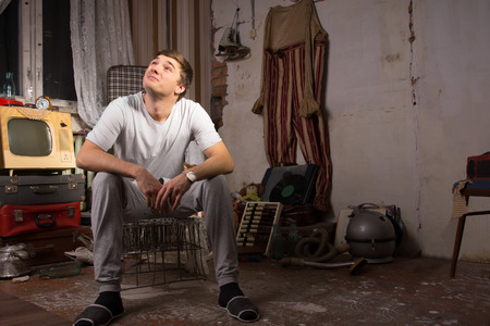 junked: Young Handsome Man in Casual Shirt Sitting on Cage at Messy Junked Room Looking Up
