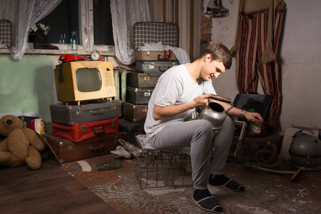 oddity: Happy Young Man in Casual Outfit Sitting on Cage, Holding Unused Kettle at the Junk Room Stock Photo