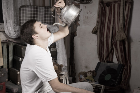 oddity: Monochrome Style of Young Man Drinking Something From Old Kettle at the Junk Room.