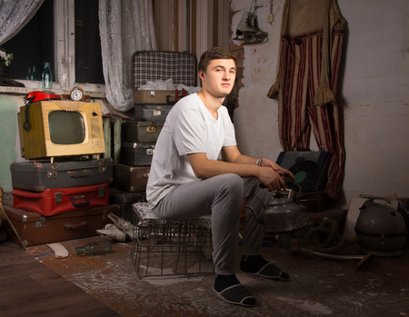 oddity: Young Man in Casual Outfit Sitting at the Junk Room Looking at Camera.