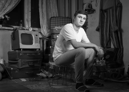 casual fashion: Monochrome Capture of Young Man in Casual Fashion Sitting on the Cage at the Junk Room While Looking at Camera. Stock Photo