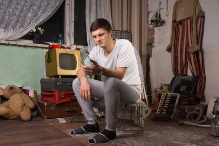 unmotivated: Young Man in Casual Clothing Sitting on Cage While Holding a Bottle at Junk Room.