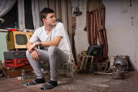 negligent: Young Handsome Man Sitting on Cage at the Junk Room Looking at Right Frame. Stock Photo