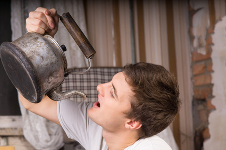 oddity: Close up Young Handsome Man Drinking From Vintage Kettle Inside a Room.