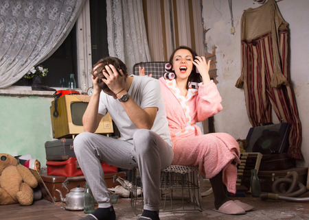 uneducated: Couple in a squalid room having an argument as they sit on a wire crate with the man holding his head in his hands and the wife in her dressing gown venting her anger