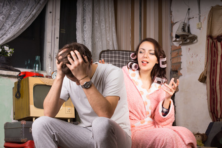 slovenly: Couple in a run down retro room sitting arguing with the wife in her dressing gown gesturing and talking while the man covers his ears