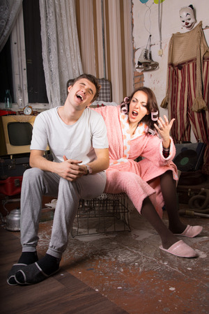 slovenly: Handsome young man yelling in frustration at his wife at her constant nagging as they sit together in a squalid run down retro sitting room